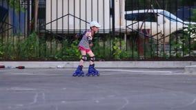 盖帽的小女孩在溜冰鞋乘坐 股票视频