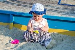 盖帽的小女孩婴孩使用与在一个沙盒的玩具与在操场的沙子 库存图片
