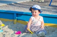 盖帽的小女孩婴孩使用与在一个沙盒的玩具与在操场的沙子 免版税图库摄影