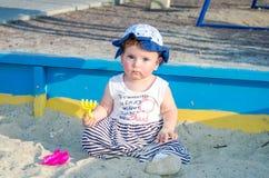 盖帽的小女孩婴孩使用与在一个沙盒的玩具与在操场的沙子 库存照片
