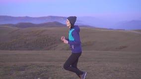 盖帽的少妇运动员在背景山,缓慢的mo跑 股票录像