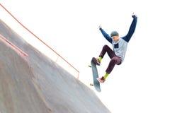 盖帽的少年溜冰板者做与一个跃迁的一个把戏在skatepark的舷梯 被隔绝的溜冰者和舷梯  图库摄影