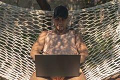 盖帽的年轻人,坐在膝上型计算机,自由职业者,5 g连接,工作的一个吊床的夏天衣裳在度假, 免版税库存照片