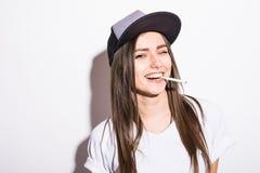盖帽的性感的抽烟的美丽的妇女有雪茄特写镜头演播室射击的 免版税图库摄影