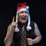 盖帽的情感喜剧演员人有辫子的姿势示意,预期圣诞节和新年 免版税库存图片