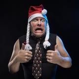 盖帽的情感喜剧演员人有辫子的姿势示意,预期圣诞节和新年 图库摄影