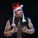 盖帽的情感喜剧演员人有辫子的姿势示意,预期圣诞节和新年 库存照片