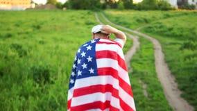 盖帽的成熟人是在路到乡下 他有在他的肩膀的美国旗子 爱国天,天记忆 影视素材