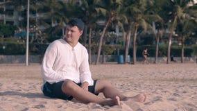 盖帽的游人并且看在旁边坐干净的海岸沙子 股票录像