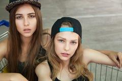 盖帽的白种人女孩在看照相机的推车 免版税库存照片