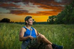 盖帽的简单的人享受自然,并且与一个瓶的沈默酒,在背景中是美好的夏天日落 免版税库存照片