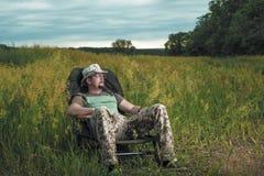 盖帽的简单的人享受自然,并且沈默,在背景中是美好的夏天日落 免版税库存照片