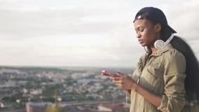盖帽的逗人喜爱的非裔美国人的女孩在她的智能手机选择音乐听 被弄脏的都市风景背景 股票视频