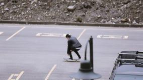 盖帽骑马的溜冰板者在停车位,做把戏 灰色天气 极其 影视素材