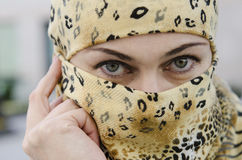 盖面孔的围巾的欧洲年轻美丽的女孩。 免版税库存图片