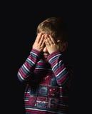 盖他的在黑背景的害怕的男孩眼睛 免版税图库摄影