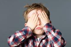 盖他的眼睛的孩子的乐趣捉迷藏是无形的 库存照片