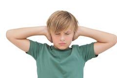盖他的耳朵的白肤金发的男孩用他的注视闭合 免版税图库摄影