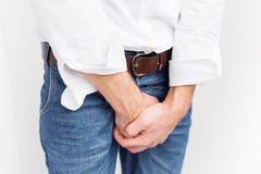 盖他的裤裆的人用两只手 免版税库存照片