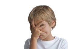 盖他的面孔用手和看照相机的男孩通过在白色背景隔绝的手指 免版税库存照片