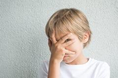 盖他的面孔用手和看照相机的男孩通过手指反对灰色背景 免版税图库摄影