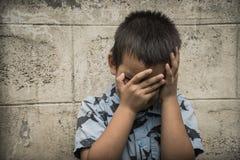 盖他的面孔的一个年轻亚裔孩子用他的胳膊 免版税图库摄影