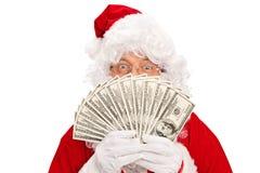 盖他的面孔的圣诞老人用金钱 免版税库存图片