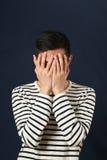 盖他的面孔的失望的年轻亚裔人由棕榈 免版税库存图片