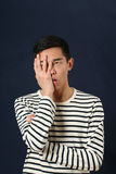 盖他的面孔的沮丧的年轻亚裔人由棕榈 库存照片
