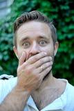 盖他的嘴的一个惊奇的年轻人的画象用手 免版税库存图片