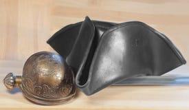 盗版三角帽子和军刀在木背景 库存照片
