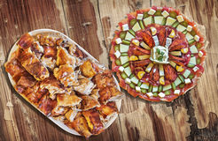 满盘与唾液烤猪肉肉集合的受欢迎的美味开胃菜盘老被风化的庭院表表面上 库存照片
