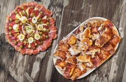 满盘与唾液烤猪肉肉集合的受欢迎的美味开胃菜盘老被风化的庭院表表面上 免版税库存图片