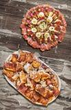 满盘与唾液烤猪肉肉集合的受欢迎的美味开胃菜盘老被风化的庭院表表面上 免版税图库摄影