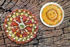 满盘与在老破裂的树桩顶面服务俄国沙拉设置的碗的开胃菜盘Meze当野餐桌 免版税图库摄影