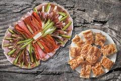 满盘与塞尔维亚传统Gibanica的开胃菜美味盘弄皱了在老破裂的木野餐桌上设置的乳酪饼 免版税库存图片
