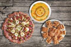满盘与Gibanica的塞尔维亚传统开胃菜Meze弄皱了乳酪饼并且装饰了在老木Surfa设置的奥利维尔沙拉 免版税库存照片