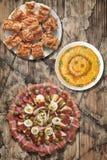 满盘与Gibanica的塞尔维亚传统开胃菜Meze弄皱了老木表面上和奥利维尔沙拉设置的乳酪饼 库存图片