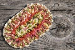 满盘传统在老被打结的破裂的木野餐桌上的开胃菜美味盘集合 库存照片