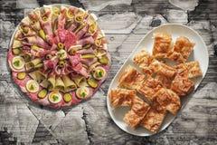 满盘传统开胃菜美味盘和Gibanica弄皱了乳酪在老破裂的片状庭院表上设置的饼切片 免版税库存照片