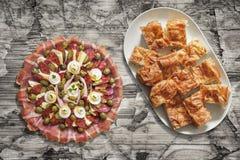 满盘传统开胃菜美味盘和Gibanica弄皱了乳酪在老破裂的片状庭院表上设置的饼切片 免版税库存图片