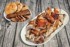 满盘唾液与在老松林野餐桌上和被发酵的皮塔小面包干大面包的烤猪肉切片设置的长方形宝石切片 库存照片
