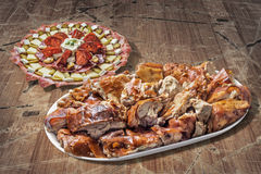 满盘唾液烤猪肉切片和在老破裂的被剥皮的木头的塞尔维亚传统开胃菜Meze集合 免版税库存图片