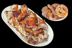 满盘唾液烤猪肉切片和椒盐脆饼与束新月形面包芝麻乳酪在黑背景隔绝的油酥点心 免版税库存图片