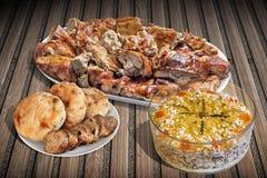 满盘唾液烤猪肉和碗与坑的奥利维尔沙拉 图库摄影