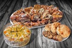 满盘唾液烤猪肉和碗奥利维尔沙拉用皮塔饼在老庭院表上和长方形宝石切片设置的面包大面包 库存图片