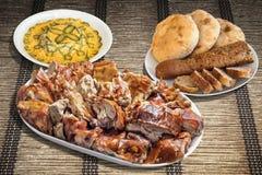 满盘唾液烤猪肉用俄国沙拉和长方形宝石缺一不可的面包用皮塔饼在羊皮纸位置字块的面包大面包 免版税库存图片