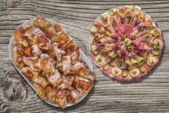 满盘唾液烤猪肉肉切片和在老土气木野餐桌上设置的开胃菜美味盘 免版税库存照片