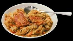 满盘圆白菜烹调与在黑背景隔绝的熏制的猪排 免版税库存照片