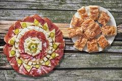 满盘塞尔维亚传统Gibanica弄皱了与食家在老破裂的野餐桌上设置的开胃菜美味盘的乳酪饼 库存照片